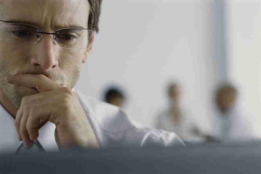 homem olhando para o computador pensativo