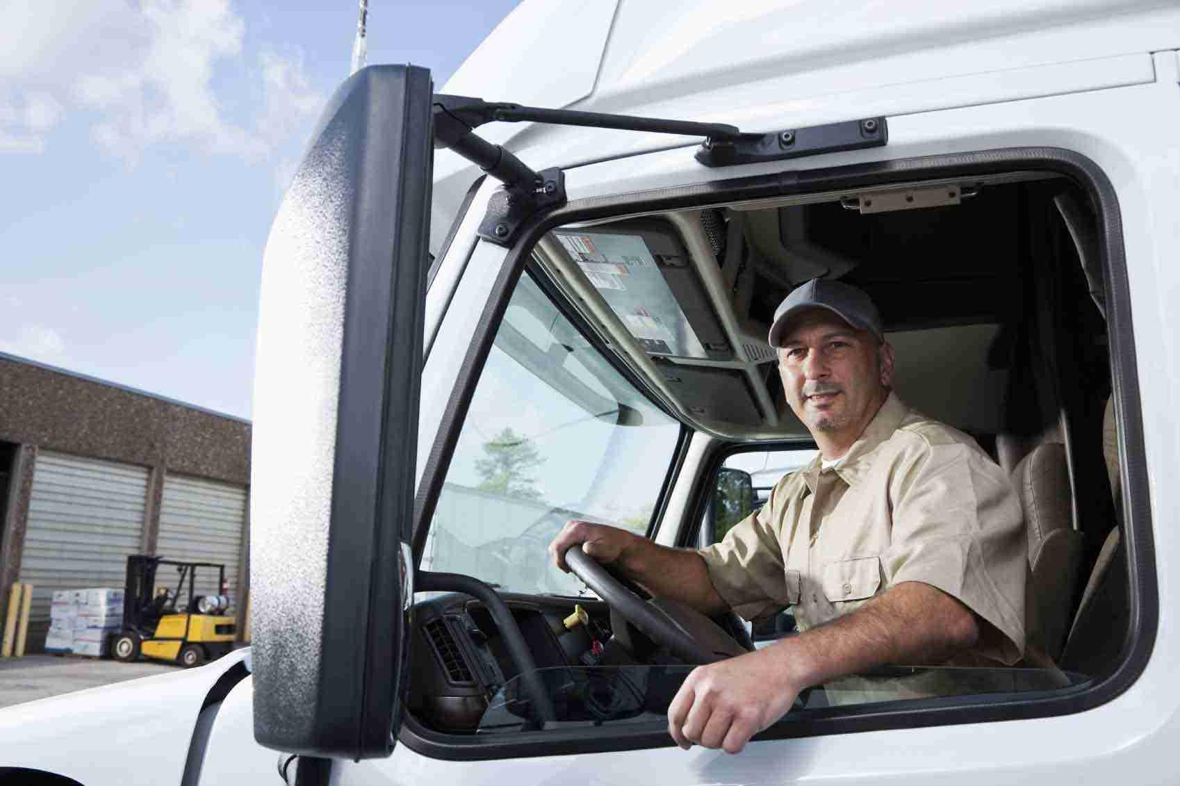 Homem dirigindo caminhão após passar pela capacitação de motorista