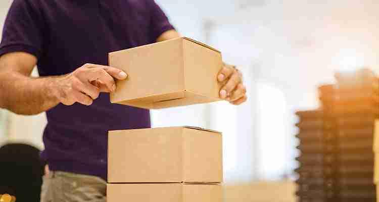 Homem posicionando caixas de papelão uma sobre a outra para agilizar o processo de coleta de mercadoria
