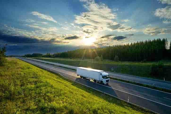 caminhão na estrada entre gramados verdes ao pôr do sol